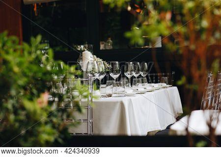 Tableware Glasses, Flower Fork, Knife Served For Dinner In Restaurant With Cozy Interior
