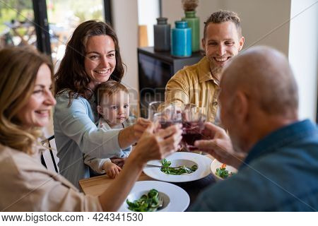 Happy Multigeneration Family Indoors At Home Eating Healthy Lunch, Clinking Glasses.