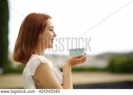 Side View Portrait Of A Happy Woman Drinking Coffee Contemplating Views In A Garden