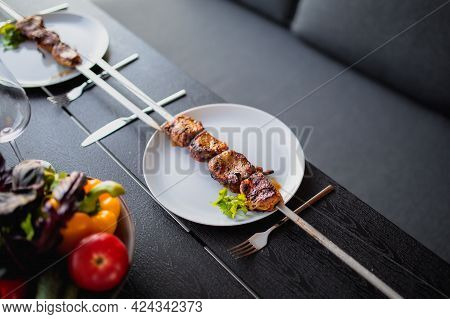 Fried meat on a skewer.Shish kebab on a plate.Skewer with a kebab and a glass of wine.Dinner on the