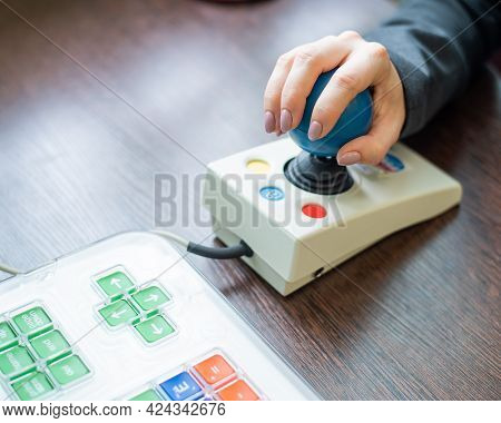 Woman With Cerebral Palsy Works On A Specialized Computer Mouse.