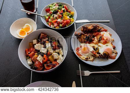 Cooked Scrambled Eggs With Salad. Shakshuka Serving On The Summer Terrace. Breakfast Outside. Fried