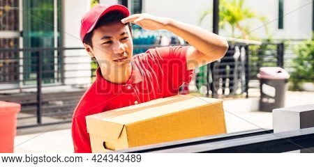 Happy Delivery Man In Red Uniform Holding Cardboard Box Standing Near House Of Customer.courier Serv