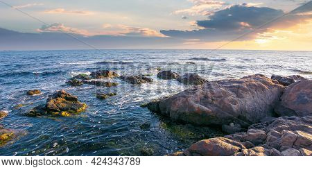 Stones On The Sea Shore In The Morning. Beautiful Summer Seascape In Purple Light. Few Clouds On The