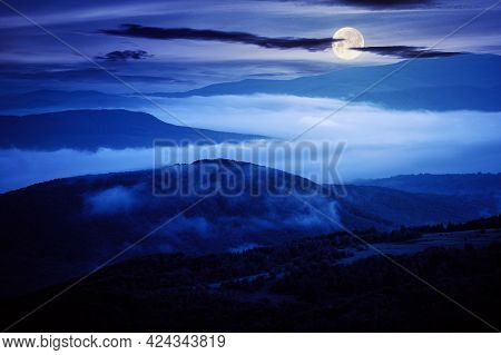 Glowing Fog In The Rural Valley At Night. Beautiful Mountain Landscape In Full Moon Light. View From