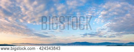Fluffy Clouds On The Azure Sky At Sunrise. Beautiful Nature Background. Panoramic View In Golden Mor