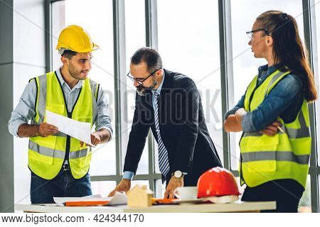 Professional Of Team Engineer Cargo Foreman In Helmets Working With Blueprint And Construction Tool