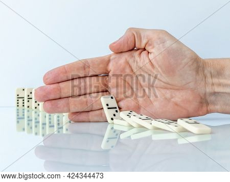 Hand Stopping Domino Effect Falling. Concept With A Solution And Intervention.