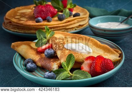 Pancakes with berries and sour cream on dark green background.  Maslenitsa. Shrovetide. Shrove Tuesday. Pancake Day. Happy holiday, Greeting. Dessert. Serving food