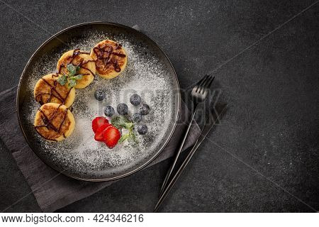 Russian cottage cheese pancakes (Syrniki) with berries, powdered sugar, chocolate sauce on ceramic  plate on black background. Top view with copy space. Dessert. Serving food
