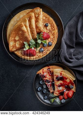 Pancakes with berries  and sweet sauce on black background. Top view. Maslenitsa. Shrovetide. Shrove Tuesday. Pancake Day. Happy holiday, Greeting. Dessert. Serving food