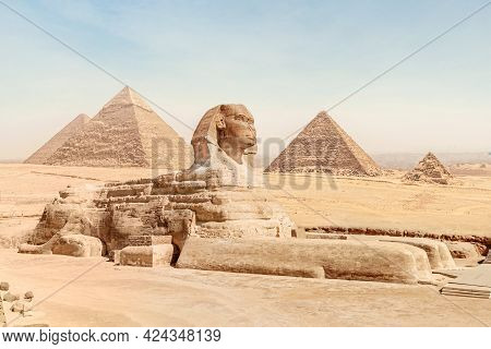 The Great Sphinx With The Body Of A Lion And The Face Of A Pharaoh Lies On The Sand Against The Back