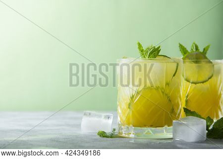 Two Glasses Of Refreshing Drinks With Ice Cubes, Juice And Lime Fruit. Party Cocktails