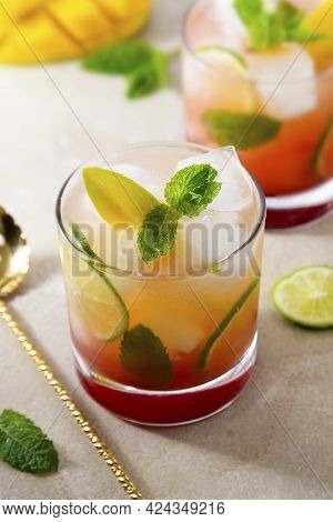 Refreshing Summer Pink Cocktail Made With Fresh Mango Juice, Ice Cubes And Mint
