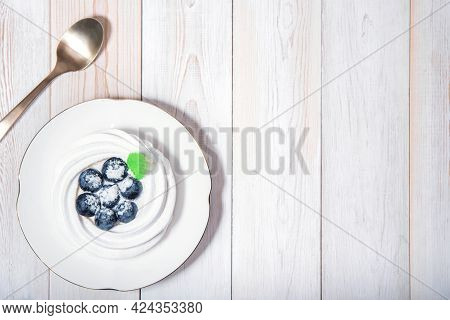 Top View On Healthy Vegan Dessert Anna Pavlova On White Wooden Table With Coffee Spoon. Meringue Swe