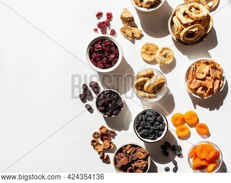 Various Dried Fruits And Berries. Flat Lay Dried Or Sun-dried Berries And Fruits In Bowls On White B