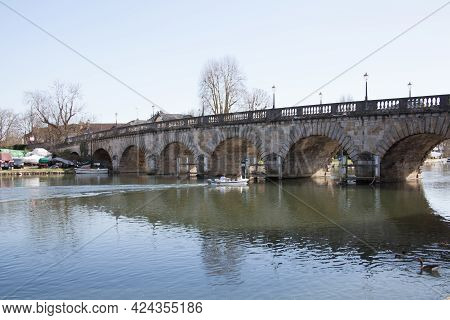 People On A Small Boat Going Under Maidenhead Bridge In Maidenhead, Berkshire In The Uk, Taken On Th