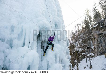 Alpinist Woman With Ice Climbing Equipment, Axe And Climbing Ropes, Climbing At A Frozen Waterfall,