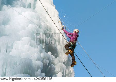 Female Ice Climber Hiking A Frozen Waterfall, Pushing Axe Pick Into The Slope And Moving Up To The T