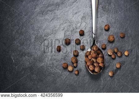 Top View Of Allspice In Teaspoon On Black Slate Background With Copy Space.