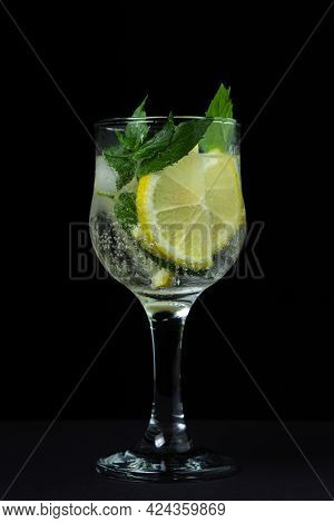 Refreshing Cocktail With Ice, Lemon And Mint On A Black Background. Non-alcoholic Cocktail.