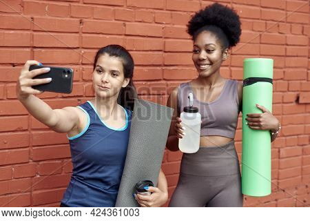 Image Of Amazing Young Athletic Women Taking A Selfie Against A Brick Wall. Smiling Black Women Spen