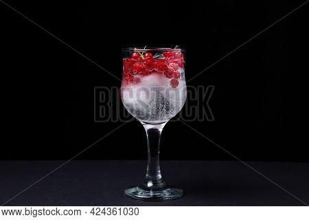 Refreshing Cocktail With Ice And Red Currants On A Black Background. Non-alcoholic Cocktail.