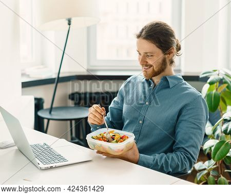 Satisfied Male Employee Eating Vegetarian Food, Pasta With Vegetables, Holding Plastic Container Wit