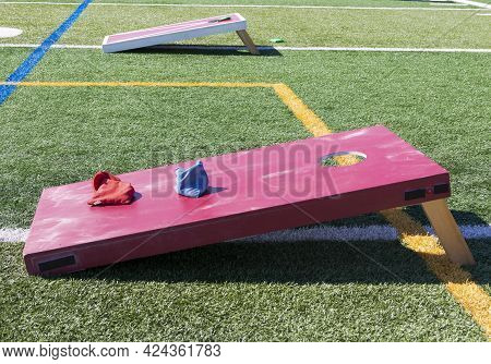 Side View Of Two Red Wooden Homemade Cornhole Games On A Green Turf Field With Blue And Red Bean Bag