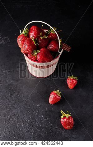 Strawberry In Light Bucket And Next To It On Black Background, Vertical Orientation, Copy Space