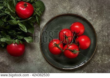 Bunch Or Branch Of Ripe Tomatoes On Ceramic Plate, Next To Spinach And Parsley. Concept Of Complimen