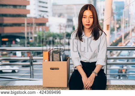 Stressed And Worried Young Asian Woman With Box Of Items Sitting Alone After Being Laid Off From Job