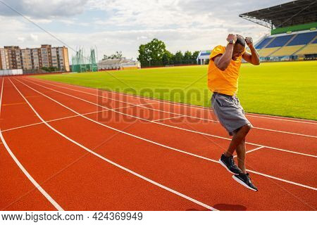 Joyful Afro American Runner In Yellow Sportswear Happily Jumping And Winning The Runner Competition,