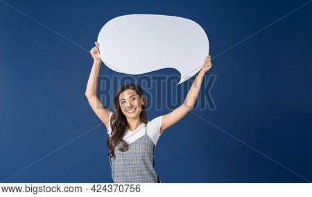 Happy Young Smiling Asian Woman Holding And Pointing To Copy Space Empty Message Bubbles On Blue Col