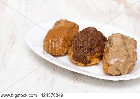 Choclate Eclairs On White Dish On Wooden Background