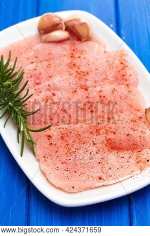 Raw Turkey With Pepper And Rosemary On White Dish