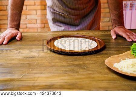 Man In Apron. Flatbread Pita On A Round Wooden Cutting Board. Bakery. Flat Bread