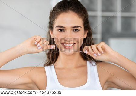 Happy Woman Holding Teeth Floss Smiling To Camera In Bathroom