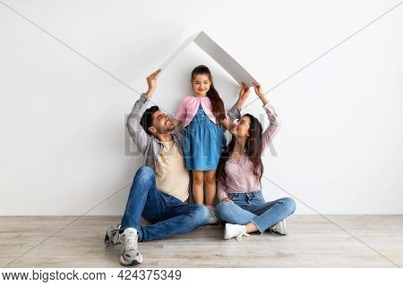 Housing For Young Family Concept. Young Eastern Father, Mother And Daughter Under Symbolic Roof Over