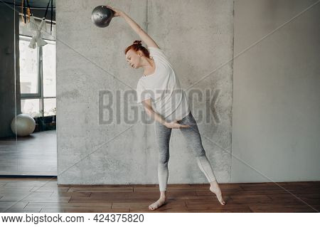 Full Length Of Beautiful Slender Red Haired Lady Standing Barefoot In Second Position With Fitball I