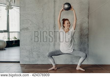 Full Leghth Shot Of Slim Happy Ginger Female Performing Barre Exercises With Small Fitball Lifted Up