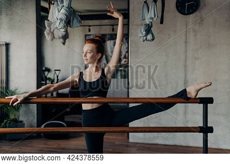 Athletic Red Haired Woman In Sleeveless Black Top Tank And Leggings Stretching Leg On Ballet Barre A