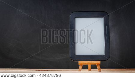 E-book Reader On The Wooden Stand At The Black Background.