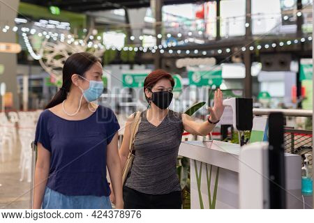 Woman Checking Body Temperature By Infrared Digital Thermometer With His Hand