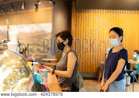 Two Female In Protective Mask Buying Coffee From Coffee Shop