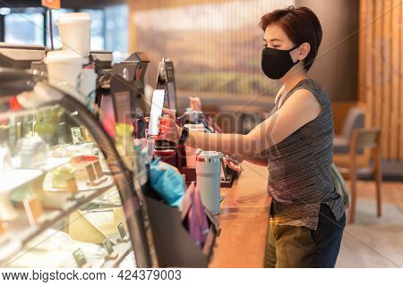 Woman Customer With Protective Mask Paying Bill By Cell Phone In Cafe