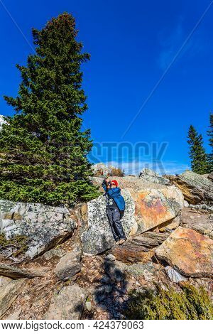 The elderly lady with enthusiasm photographs stony shore around Lake Moraine. Canadian Rockies, Province of Alberta. The concept of ecological, photographic and active tourism