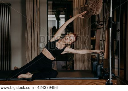 Attractive Fit Red Haired Woman With Perfect Body Shape Exercising And Stretching On Pilates Cadilla