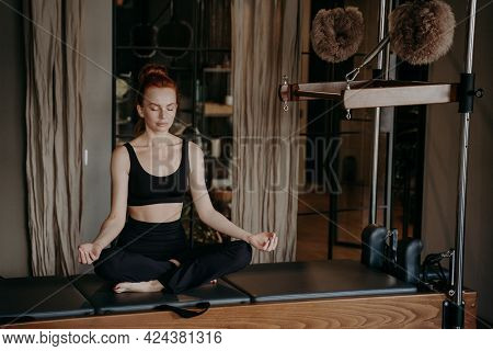 Peaceful Female Pilates Instructor Sitting In Yoga Lotus Position On Cadillac Reformer, Trying To Re