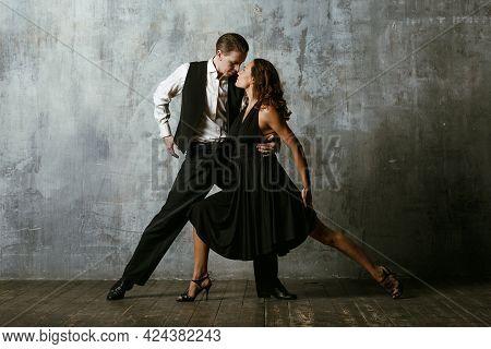 Man And Woman Dancers In Black Dress Dance Tango.